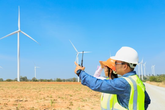 Male and female engineers look at wind turbines